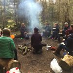Women and girls round a camp fire